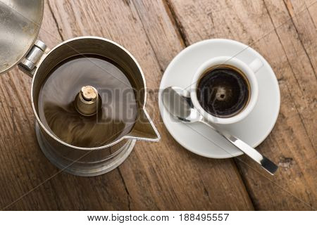 coffeepot and cup of coffee on wooden table