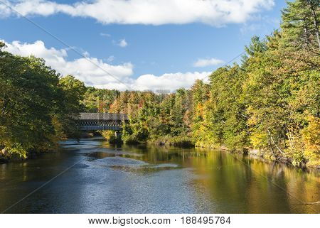 Fall foliage near covered bridge crossing Contoocook River in Henniker New Hampshire