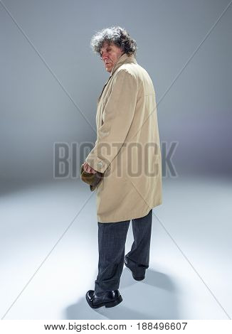 The back view of senior man in cloak as detective or mafia boss. Studio shot on gray in retro stile. Mature man with hat and suitcase