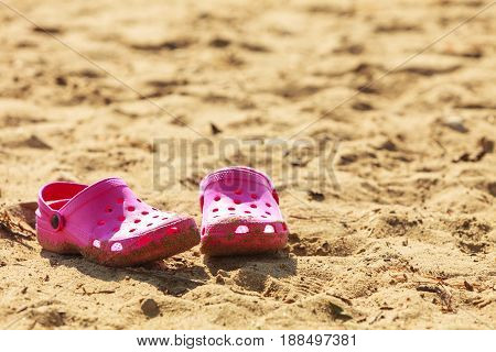 Clothes of children. Little pink female slippers on beach sand. Part of girl clothing lying on sandy floor.