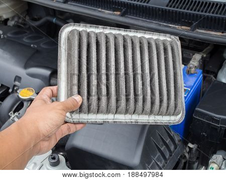 human hand hold dirty air filter in car concept of cleaning and checking air filter.