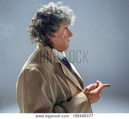 The senior man in cloak with cigar as detective or mafia boss. Studio shot on gray in retro stile