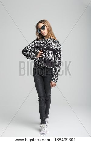 Portrait of young pretty girl with black sunglasses over gray background. woman dressed in black T-shirt, black jeans and white shoe