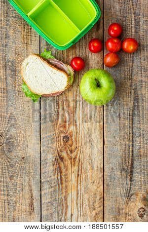 homemade lunch with apple, grape and sandwich in green lunchbox on wooden table background top view mockup