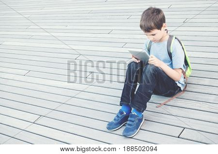 Kid using tablet computer sitting outside. School, education, learning, technology leisure concept
