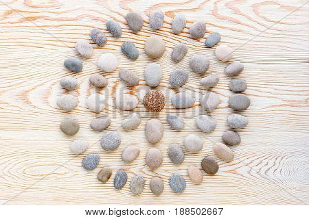 pattern of colored pebbles on white wooden background. Flat lay top view