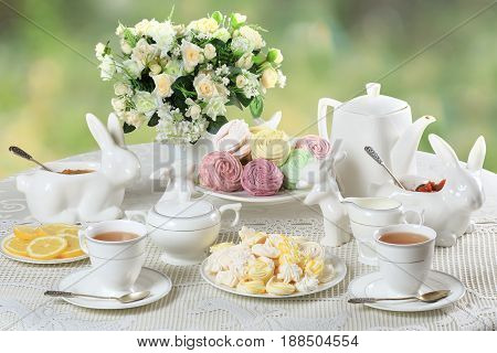 Still life with homemade marshmallows meringues and tea set with a bouquet of flowers