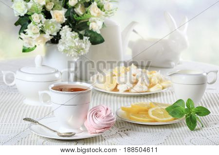 Cup of hot tea with pink marshmallow and meringues on white table with a bouquet of flowers