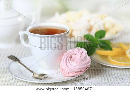 Cup of hot tea with pink marshmallow and lemon on a white table