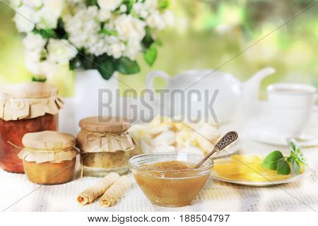 Still life with various homemade jam and tea set on a white table with a bouquet of flowers