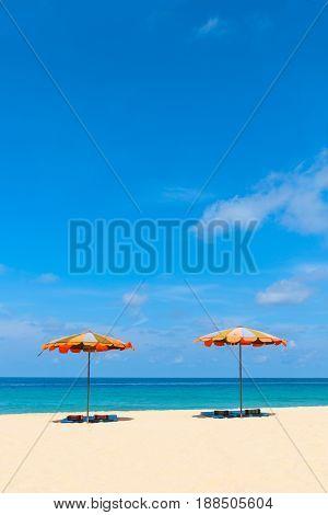 Two Empty Sunbeds And Beach Parasol Sunshades On Sand Beach
