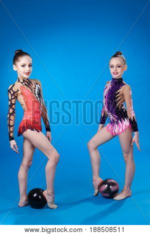Two caucasian gymnasts with a ball on a blue background