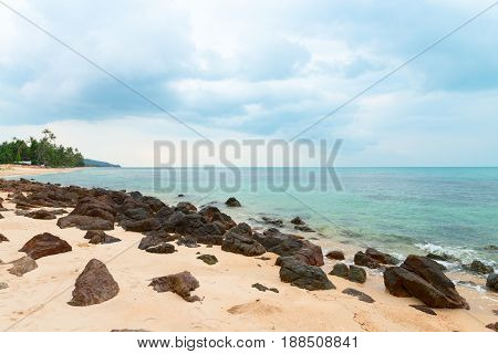Rocky Shore Under Cloudy Sky, Palm Trees On The Horizon