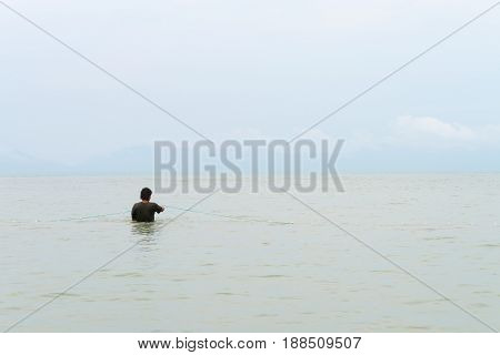 Fisherman in the sea corrects fishing net with view from his back side.