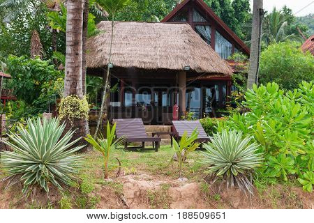 Tropical hotel resort in green nature environment with palm roof and wooden chairs