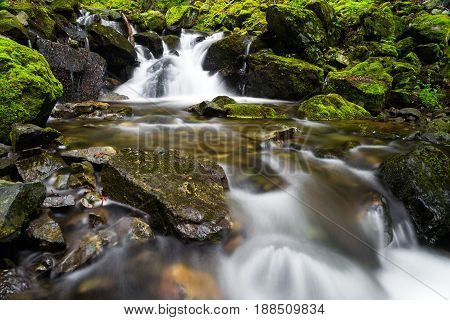 Stream cascading over bright green mossy rocks with a waterfall in the background and long exposure blurred motion on the water in the foreground