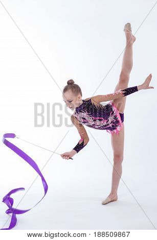 beautiful caucasian girl gymnast with Purple ribbon on a white background