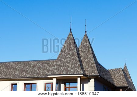 Original modern roof with turrets covered with soft grey bitumen tiles