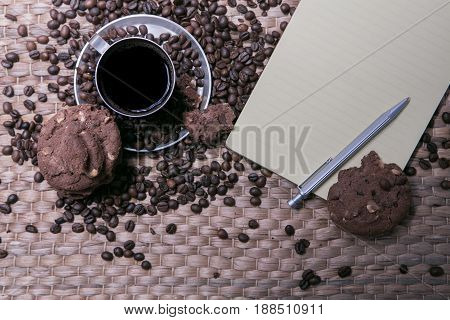 Coffee Cup And Coffee Beans On Wooden Table With Cookies And Notepad