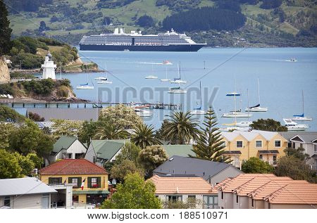 The view of Akaroa resort town and a cruise liner drifting in French Bay (New Zealand).