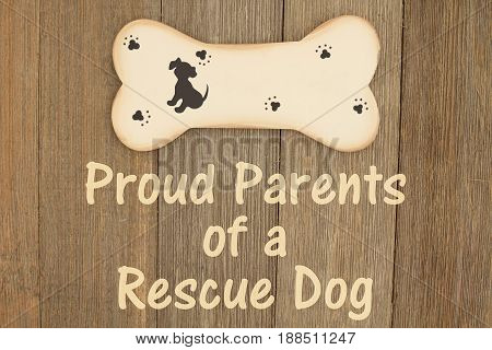 Rescuing a dog A wood dog bone on a weathered wood background with text Proud Parents of a Rescue Dog