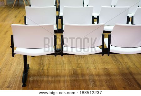 Long row chairs for the customer in office with wood floor.