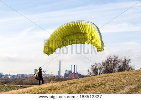 Copenhagen, Denmark - March 28, 2017:  A paraglider trying to start from a small hill just outside the city