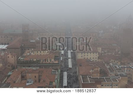 Typical red roofs of Bologna in a foggy day. View from a window of Asinelli Tower. Emilia Romagna Italy.