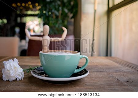 Hot mocha coffee or capuchino with white carnation flower and wood man on the wooden table
