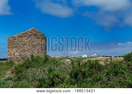 abandoned circular stone construction on a green field in Portugal