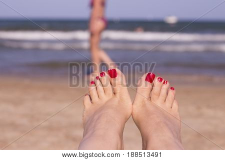 Beach scene with woman feet on the sand. Nails of feet painted red