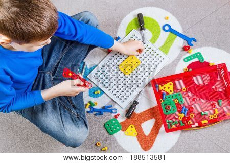Child playing with toys tool kit. Top view