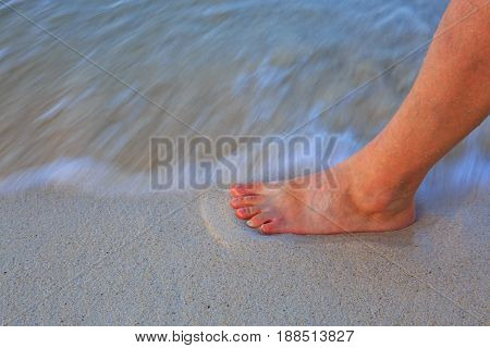 Men's leg on the sand of the beach with the sea water in the background.