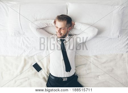 Top View. Handsome Businessman Relaxing On Bed After A Tough Day At Work