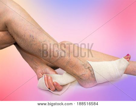 The senior woman correcting an elastic bandage which tied her leg. Varicose veins concept