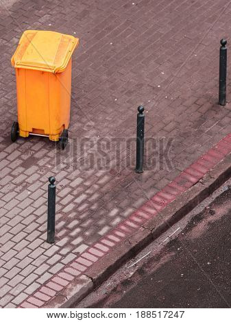Plastic orange wheely bin in the street outside waiting for garbage truck. Top view