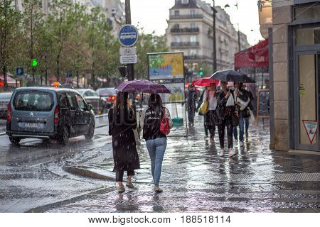 Paris, France - May 12, 2017: People with umbrella in the streets on a rainy day