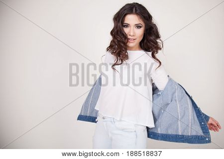 beautiful girl posing on a white background curls hairstyle denim jacket