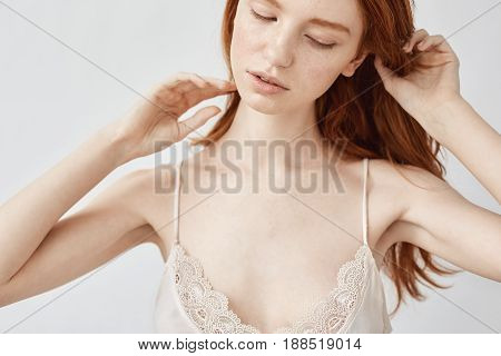 Close up photo of tender redhead girl in sleepwear posing with closed eyes over white background.