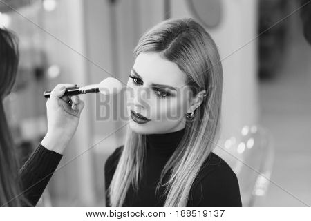 Process of making makeup. Mak-up artist working with brush on model face. Portrait of young blonde woman in beauty saloon interior. Applying tone to skin. poster