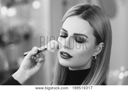 Process of making makeup. Mak-up artist working with brush on model face. Portrait of young blonde woman in beauty saloon interior. Applying tone to skin.