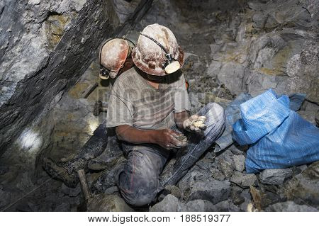 Potosi Bolivia - November 29 2013: Two miners looking for silver in the silver mine of the Cerro Rico in Potosi Bolivia.
