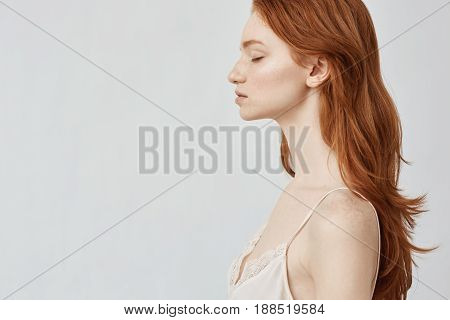 Portrait of young beautiful redhead girl in profile with closed eyes. Copy space. Isolated on white background.