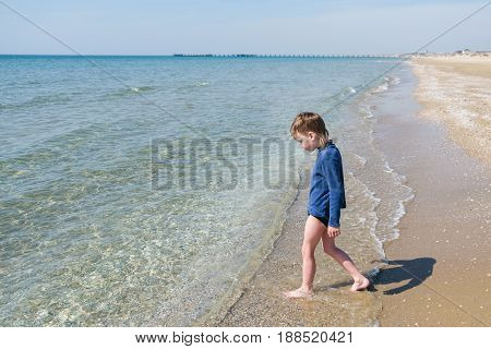 Little boy at sand beach in summer time