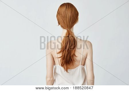 Portrait of young pretty girl with foxy hair posing standing back to camera. Copy space. Isolated on white background.