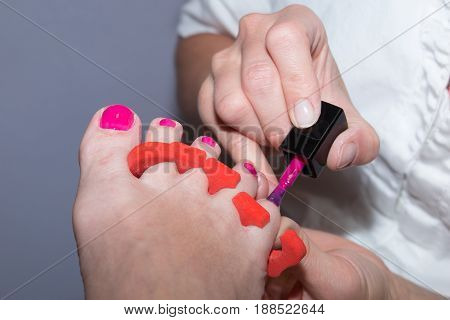 Esthetician Puts Nail Red On Her Client Feet
