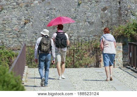 Vacationer travels in the sun by sheltering with a red umbrella