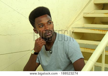 young man thinking and looking in staircase pensive portrait urban