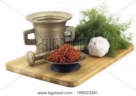Still Life Spices, Immortin saffron , marigold staminas in a copper vase on a wooden board on a background of a stern stupa for grinding spices, bunches of dill and garlic