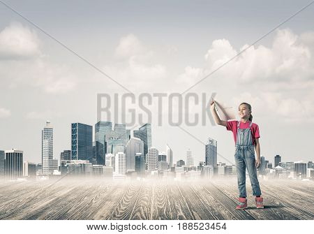 Cute kid girl standing on wooden floor with airplane
